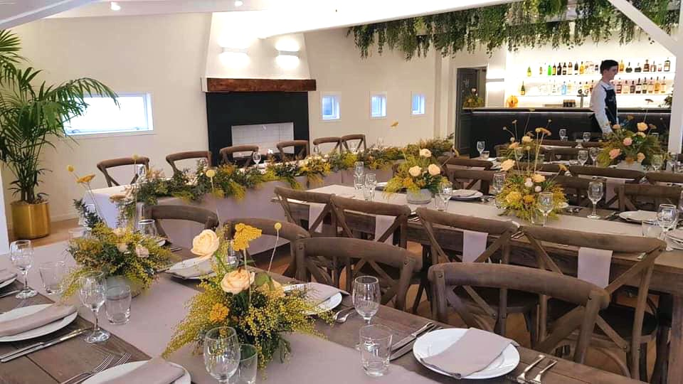 wedding venue table setup with yellow flowers and wooden chairs with modern open fireplace