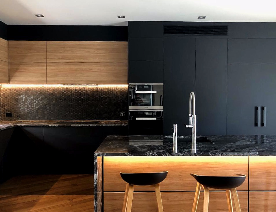 custom built matte black modern kitchen with feature lighting, black hexagonal tiles and black marble waterfall benchtop