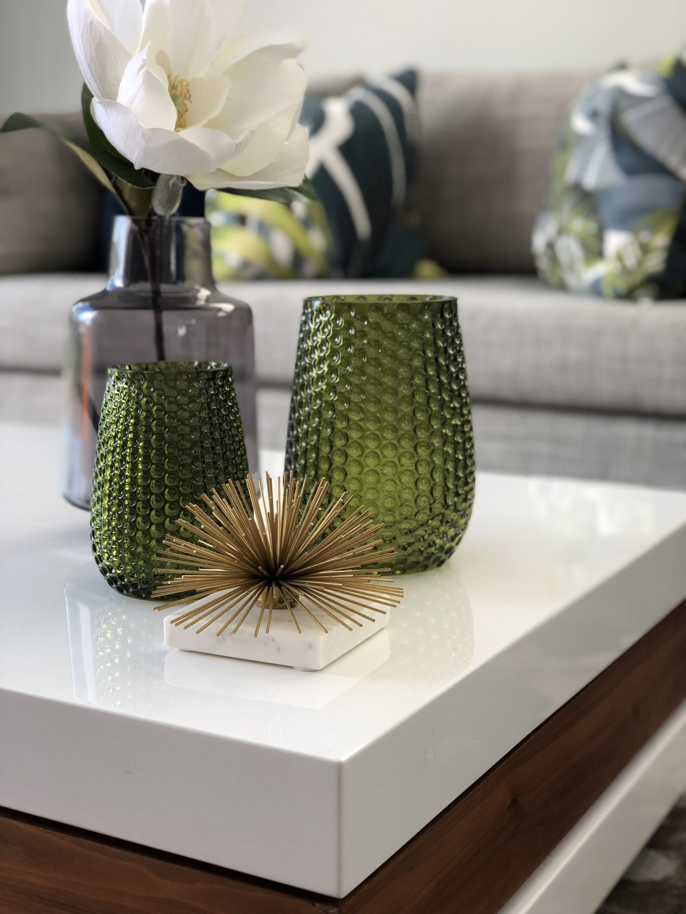 modern white gloss coffee table styling with green vases and gold ornament