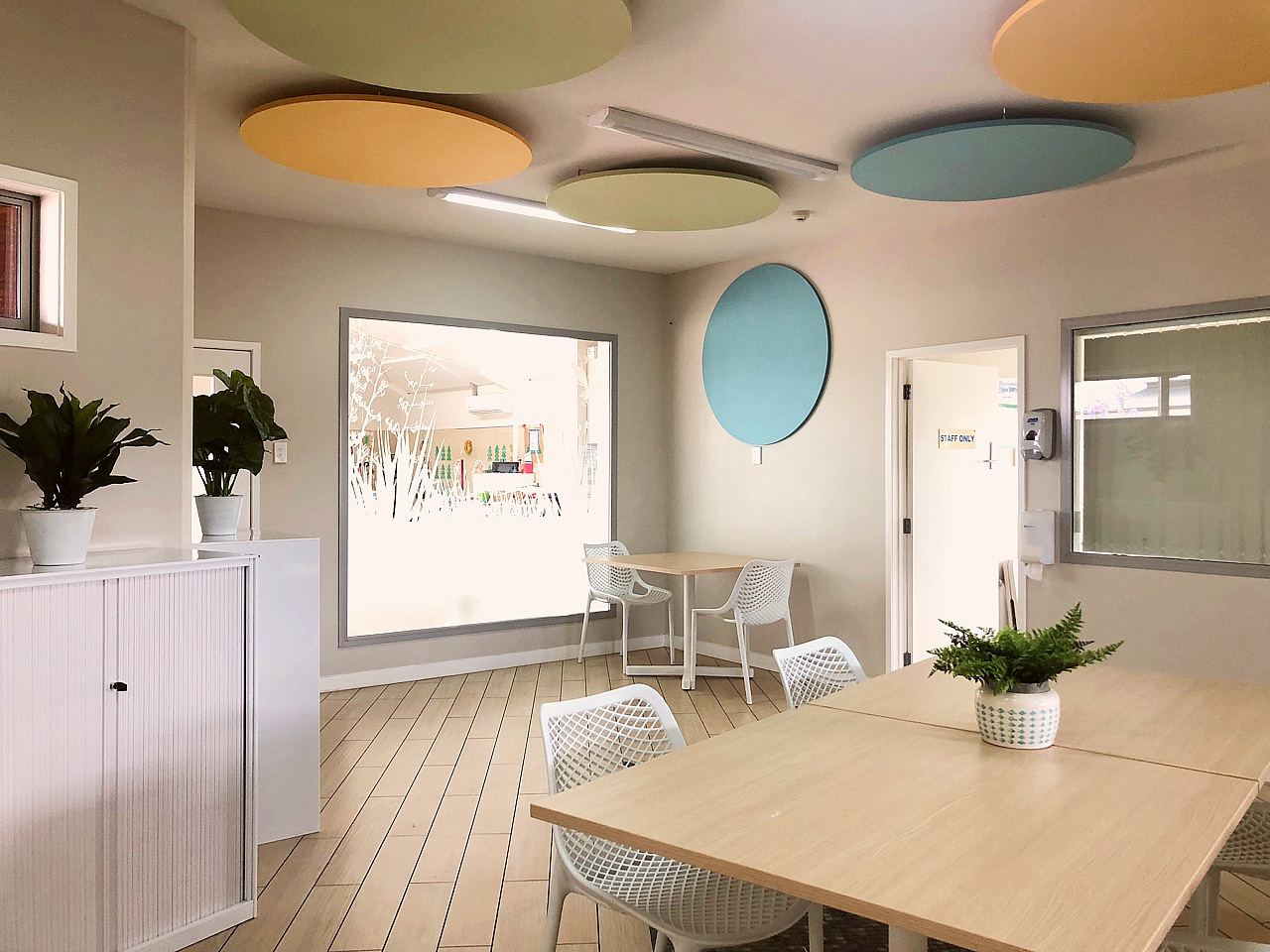 brightly coloured ceiling acoustic panels in modern staff room with laminate floors, dining table setting and window decals