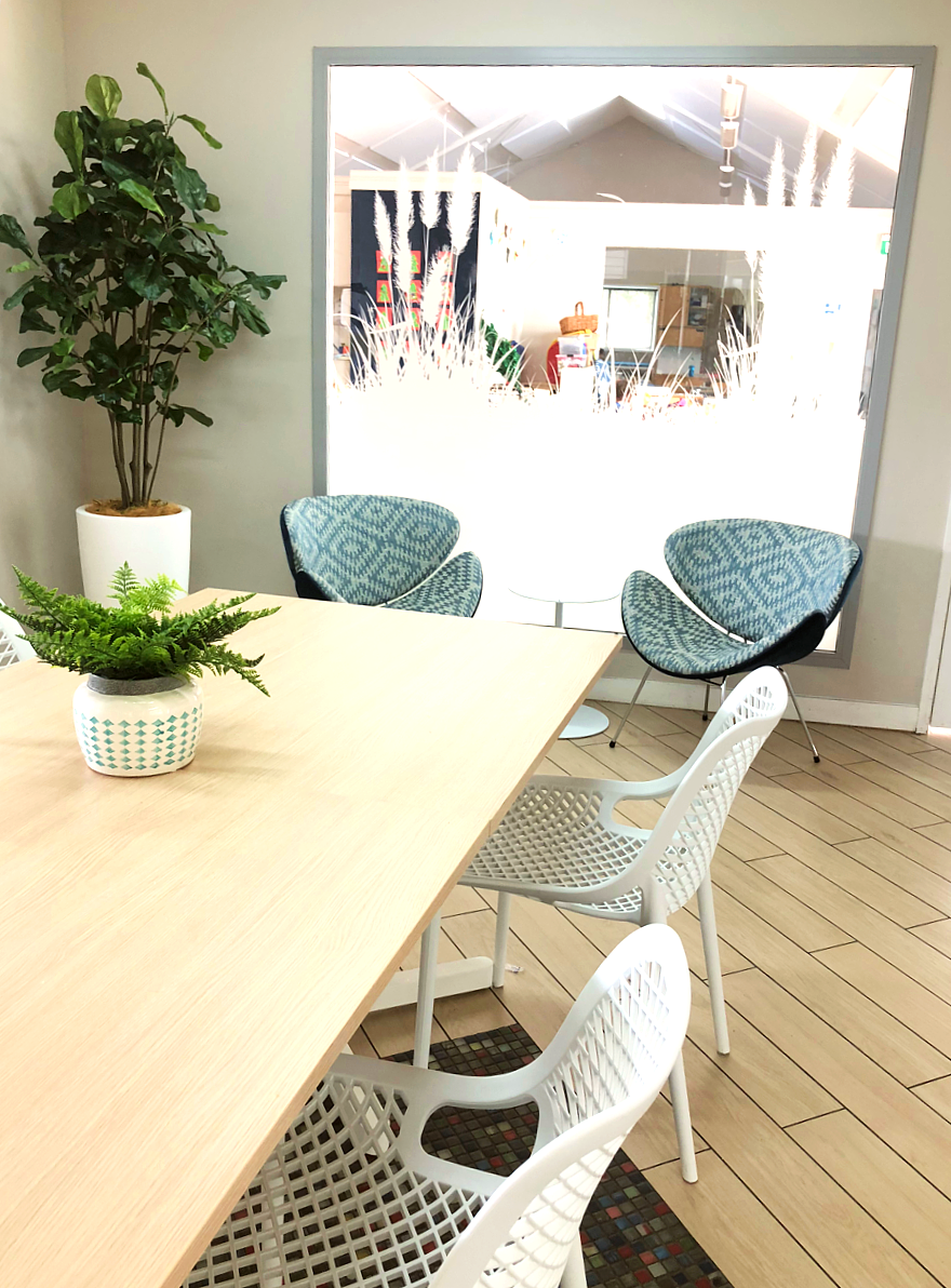 dining setting and custom made blue casual chairs in modern staff room with laminate floors and planter