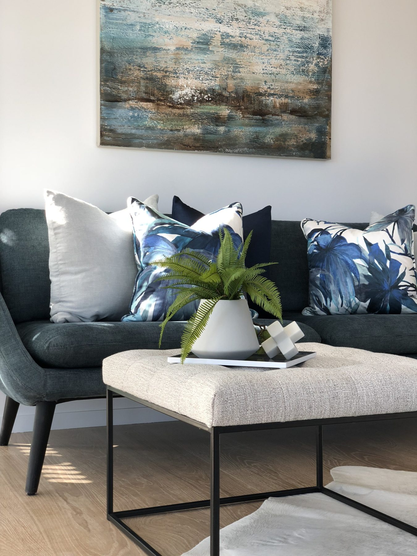 living room in modern apartment with wood floors, with curved blue couch, funky printed cushions and ottoman coffee table
