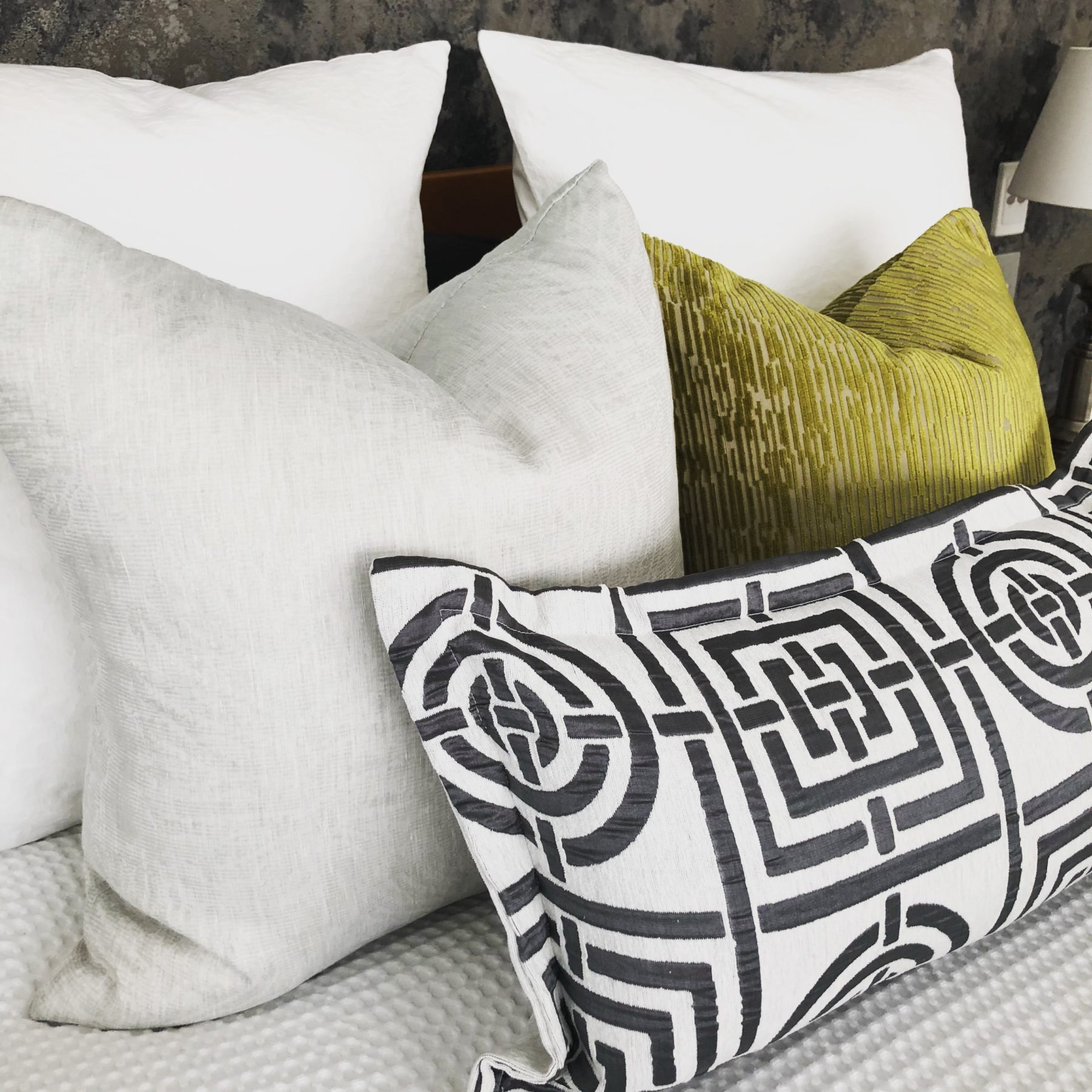 custom made velvet patterned cushions in green and grey on a king size bed