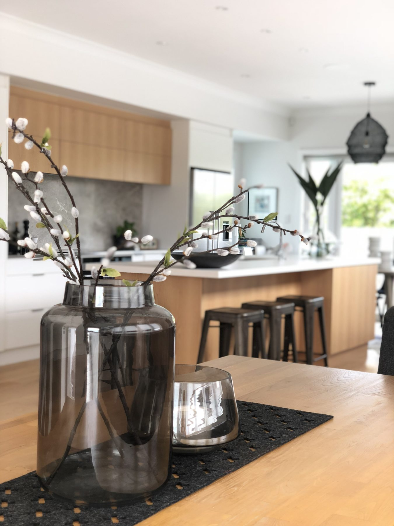 oak kitchen and dining room styling with dark glass vases and bunnytails