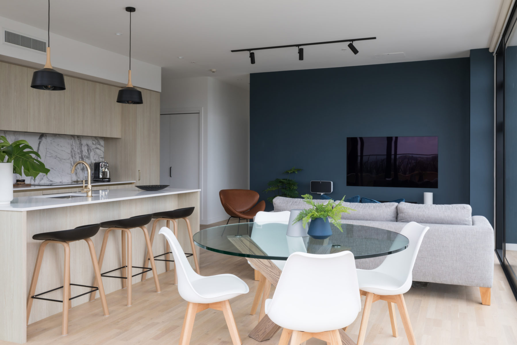 modern mount eden apartment living space with contemporary dining room, wood kitchen with brass taps and breakfast bar, blue living room wall