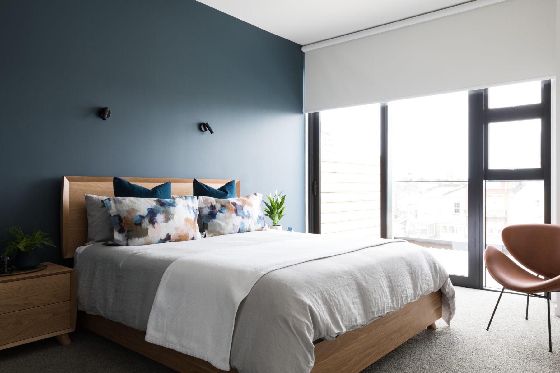 calming modern apartment bedroom with blue feature wall, solid wood furniture and leather bedroom chair