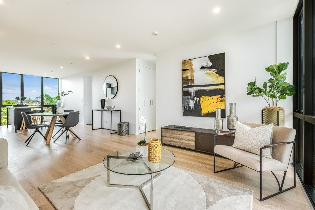 new build apartment in takapuna with high stud ceilings and wood floors. modern living and dining room with funky artwork and stylish furniture
