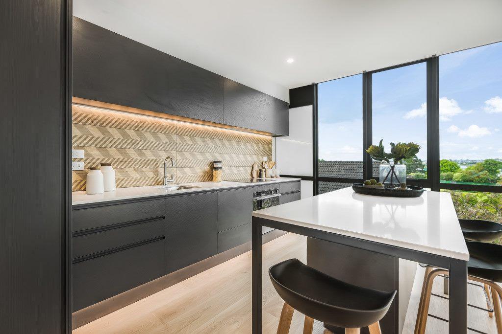 new build modern black kitchen with natural wood look chevron splashback tiles. Bar leaner with stylish bar stools