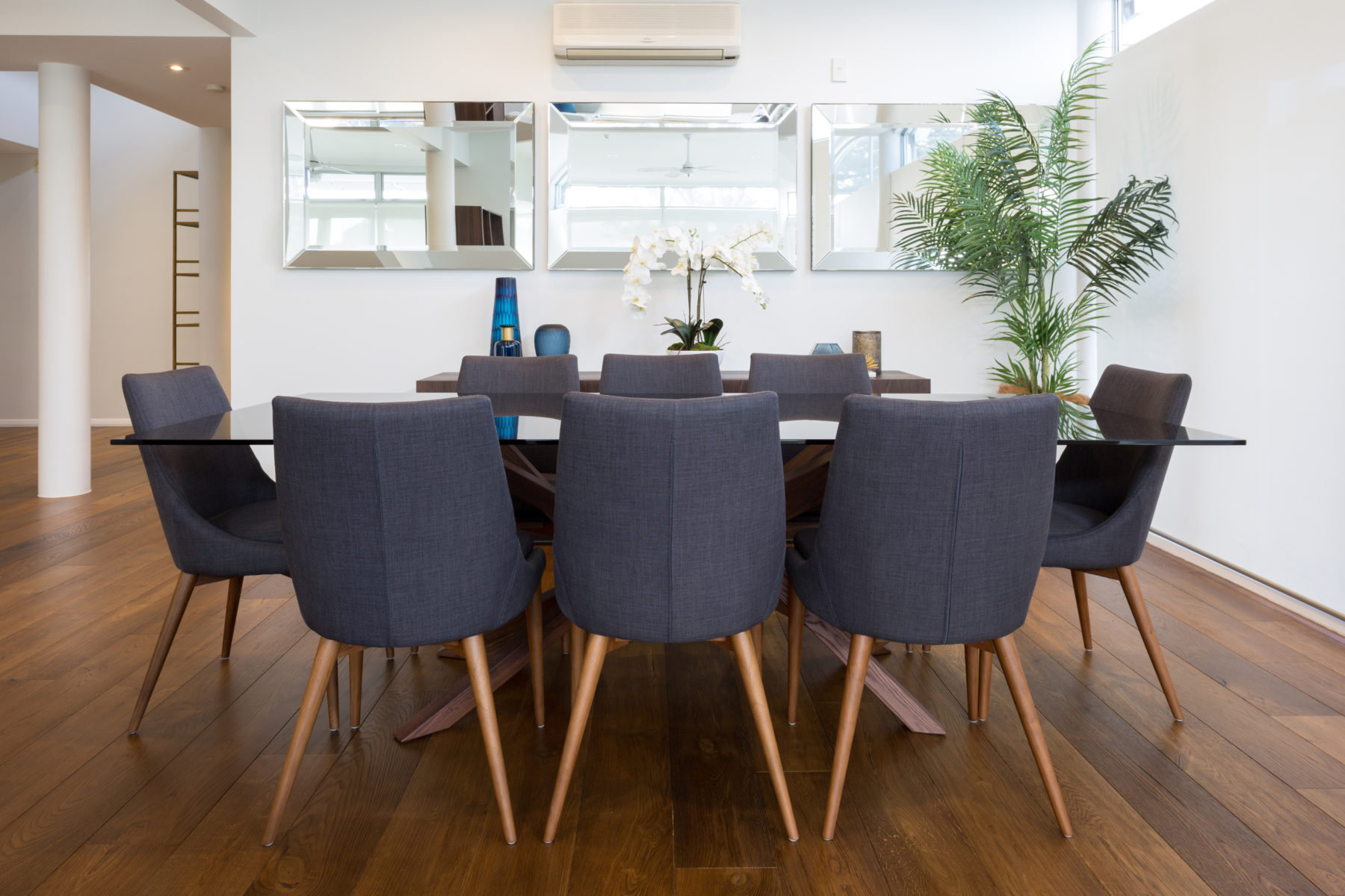 modern apartment dining room setting with wood floors and mirrors