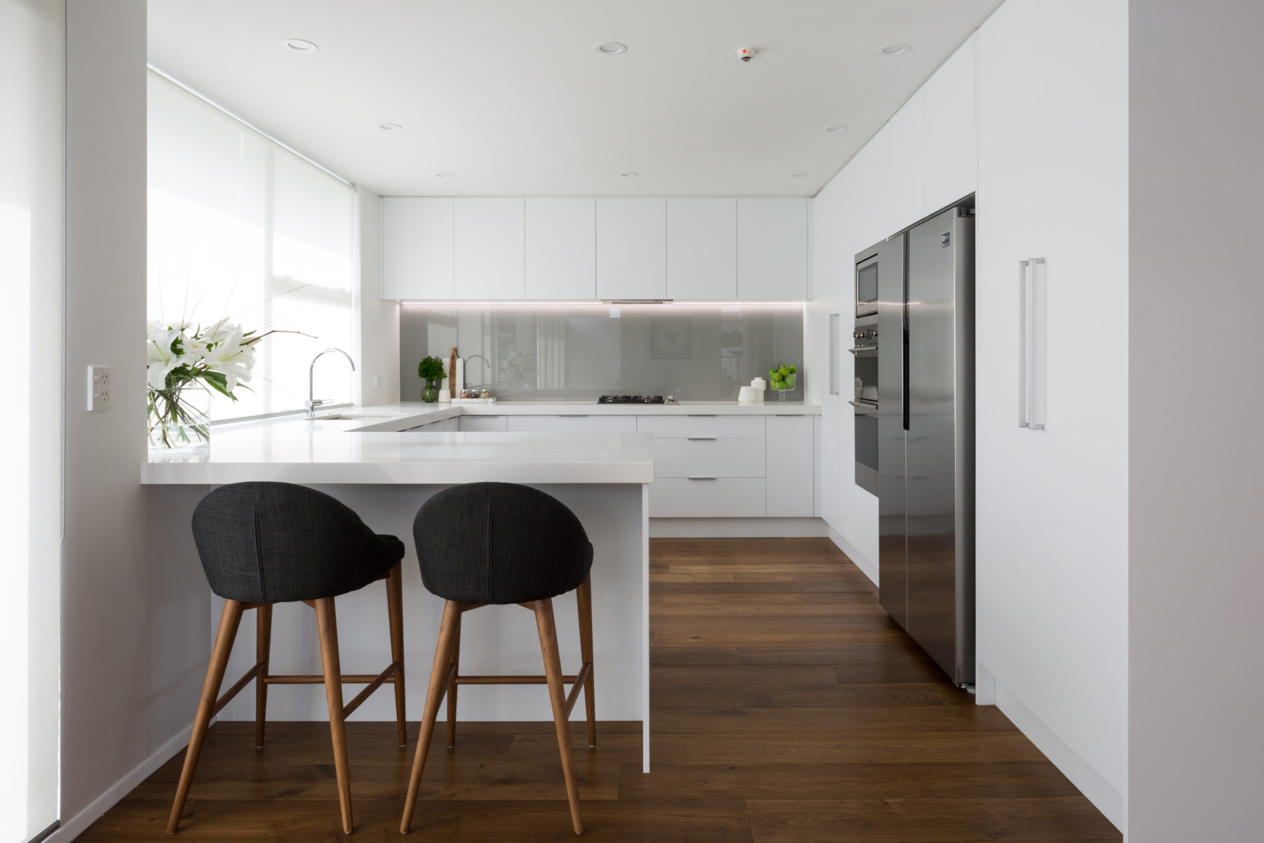 modern custom made white kitchen with green glass splashback and barstools