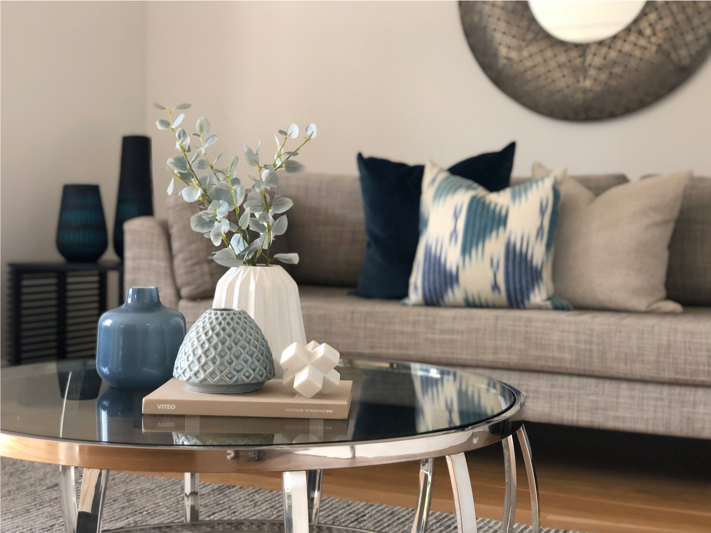 modern silver coffee table in living room with grey couch and blue velvet cushions