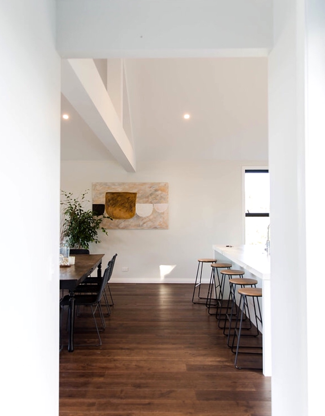 new build dining room and kitchen breakfast bar with wood floors, modern wall art