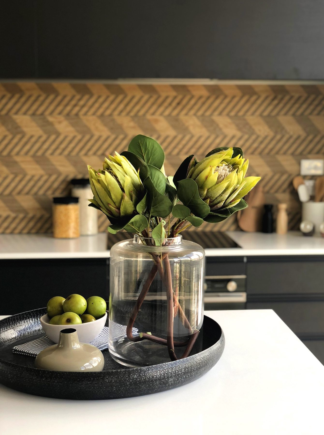 modern black kitchen with wood look chevron splashback tiles and benchtop styling