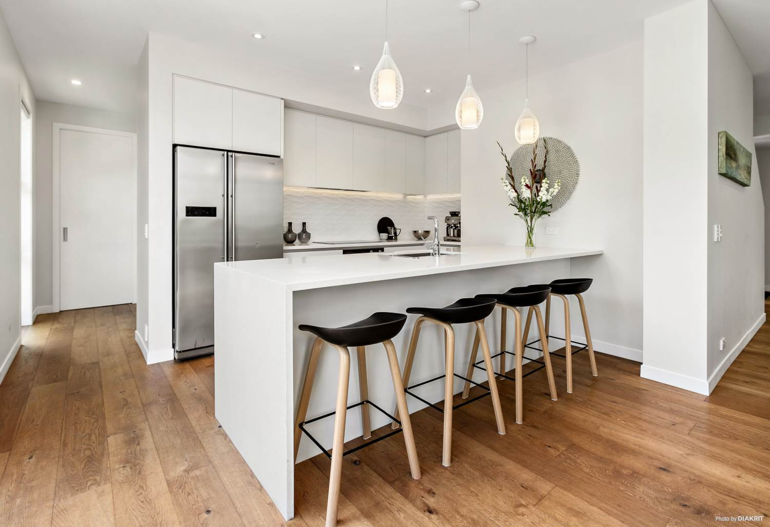 modern white kitchen with waterfall bench and wooden floors