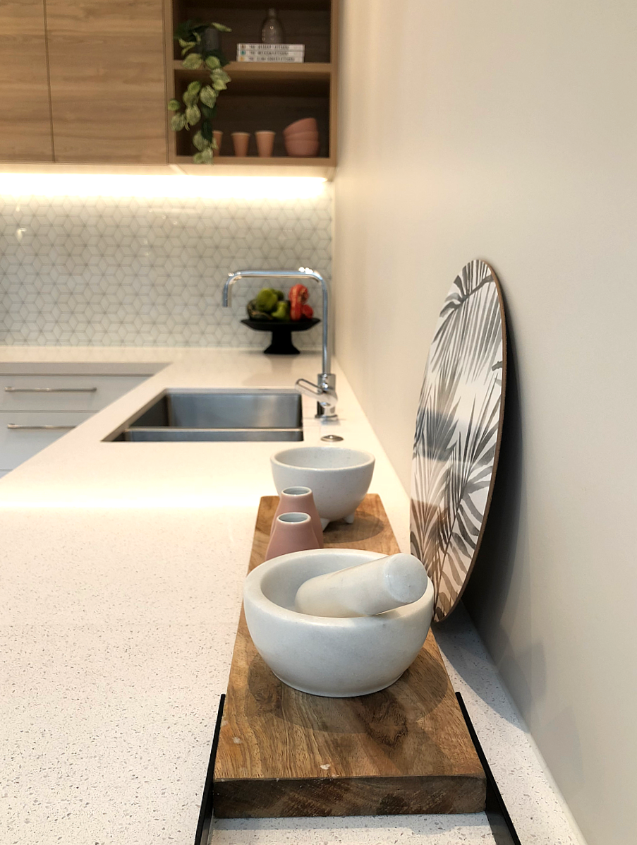 modern kitchen styling with white benchtop, wood cabinets and geometric tile splashback