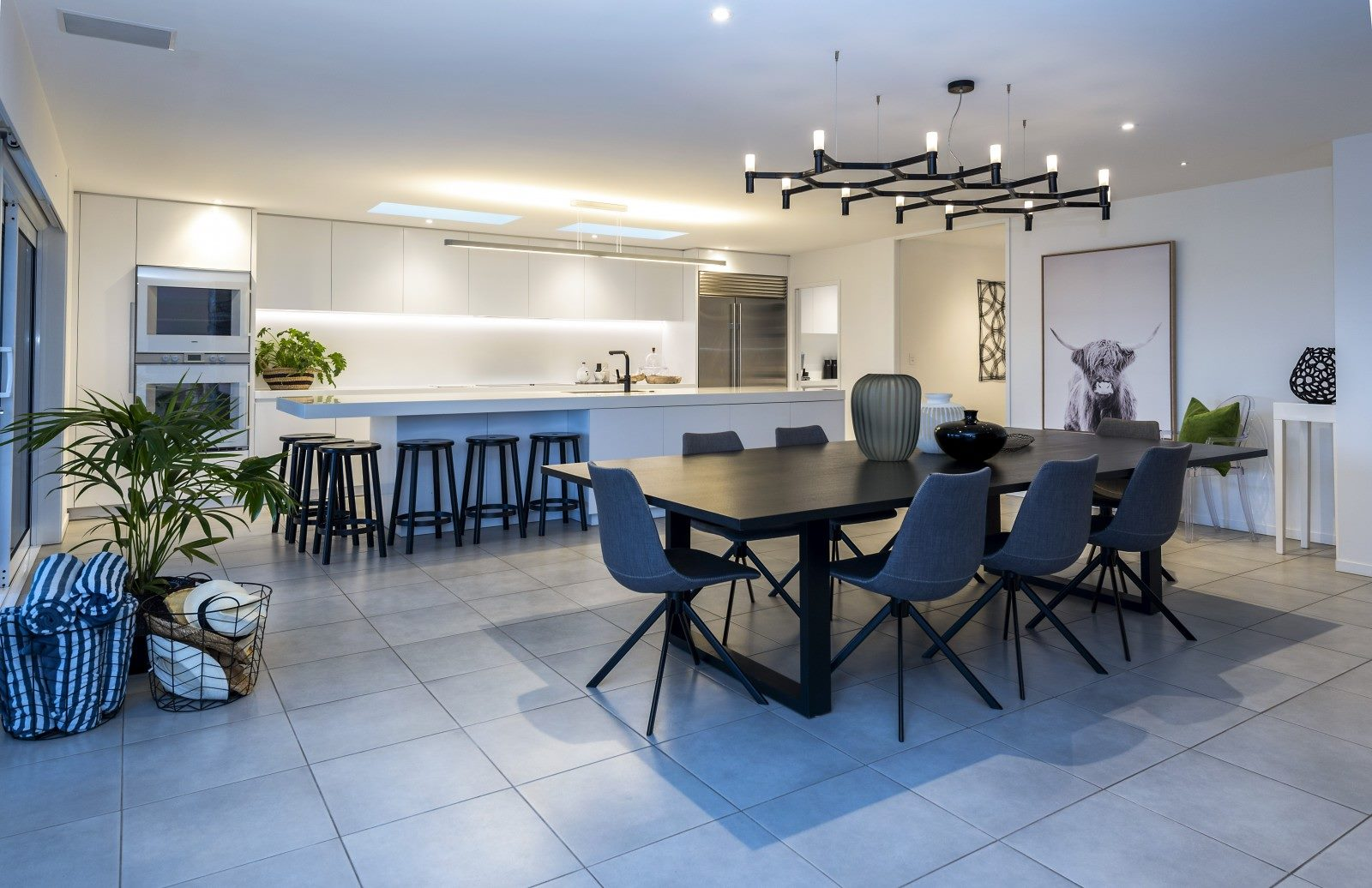 contemporary tiled kitchen dining room in high spec family home with modern art, plants and contemporary styling. kitchen with black mixer tap and double wall mounted oven