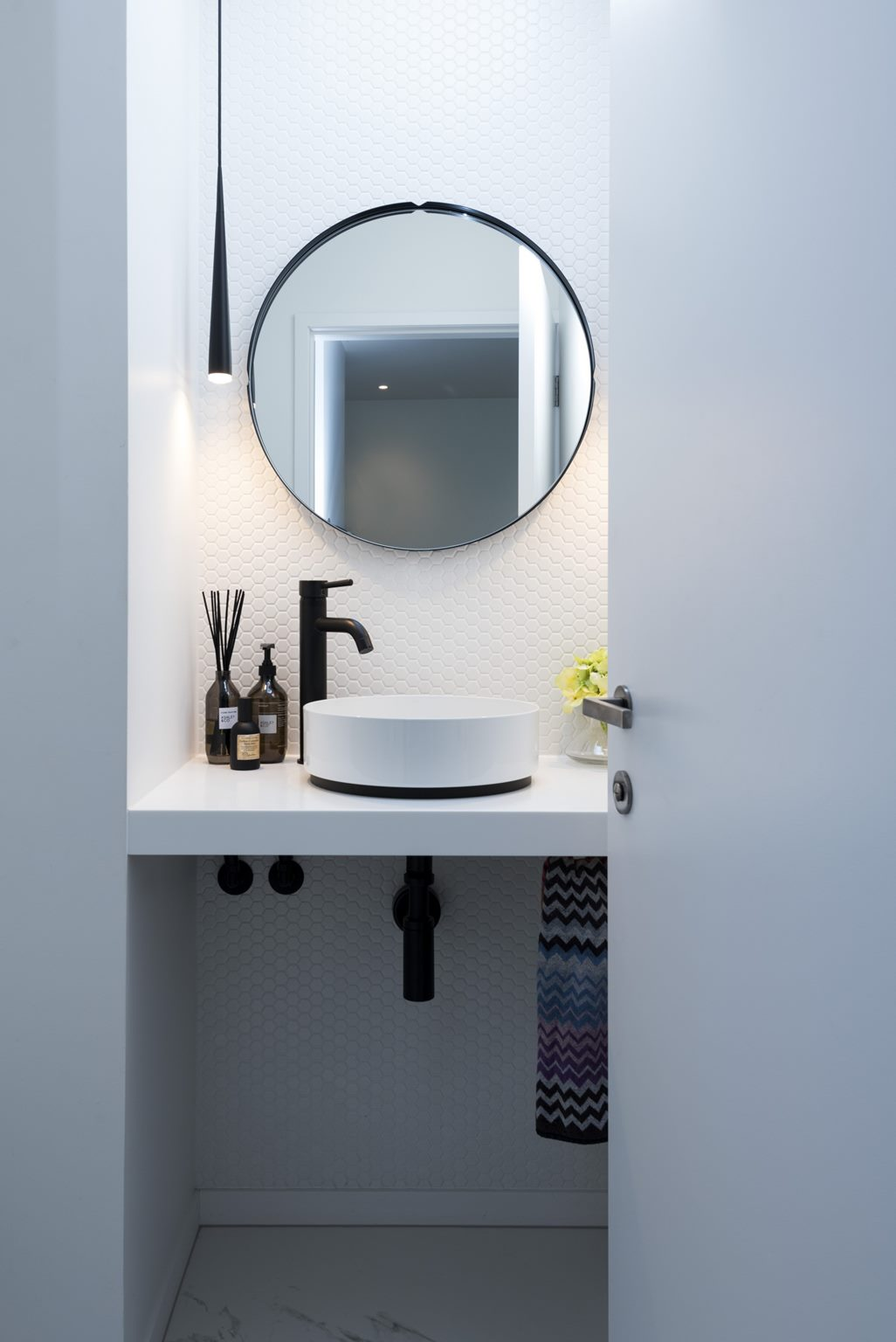 modern white bathroom design with black tapware, statement lighting, round mirror and missoni towel