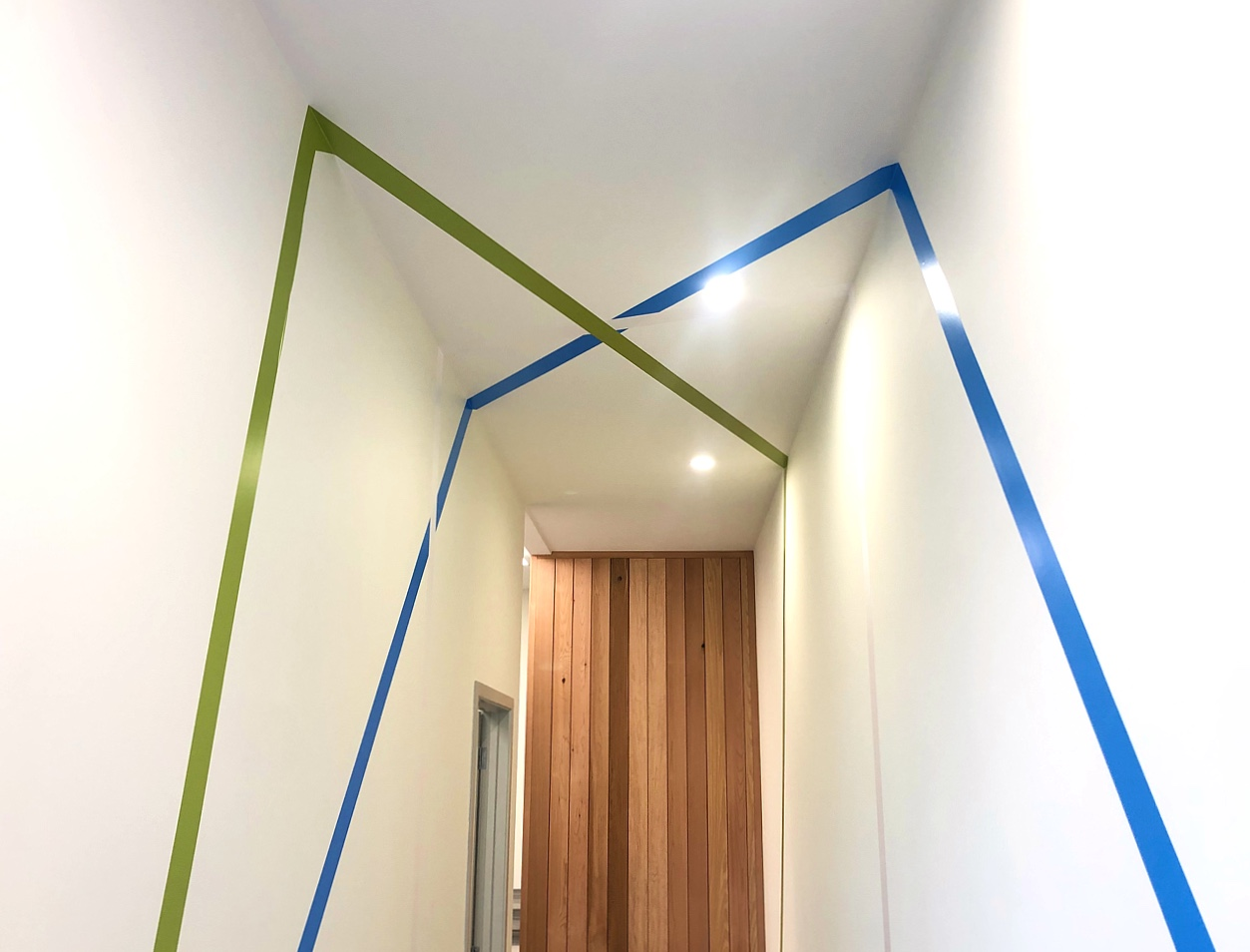 modern office hallway with cedar wood panelling and blue and green stripe wall decals