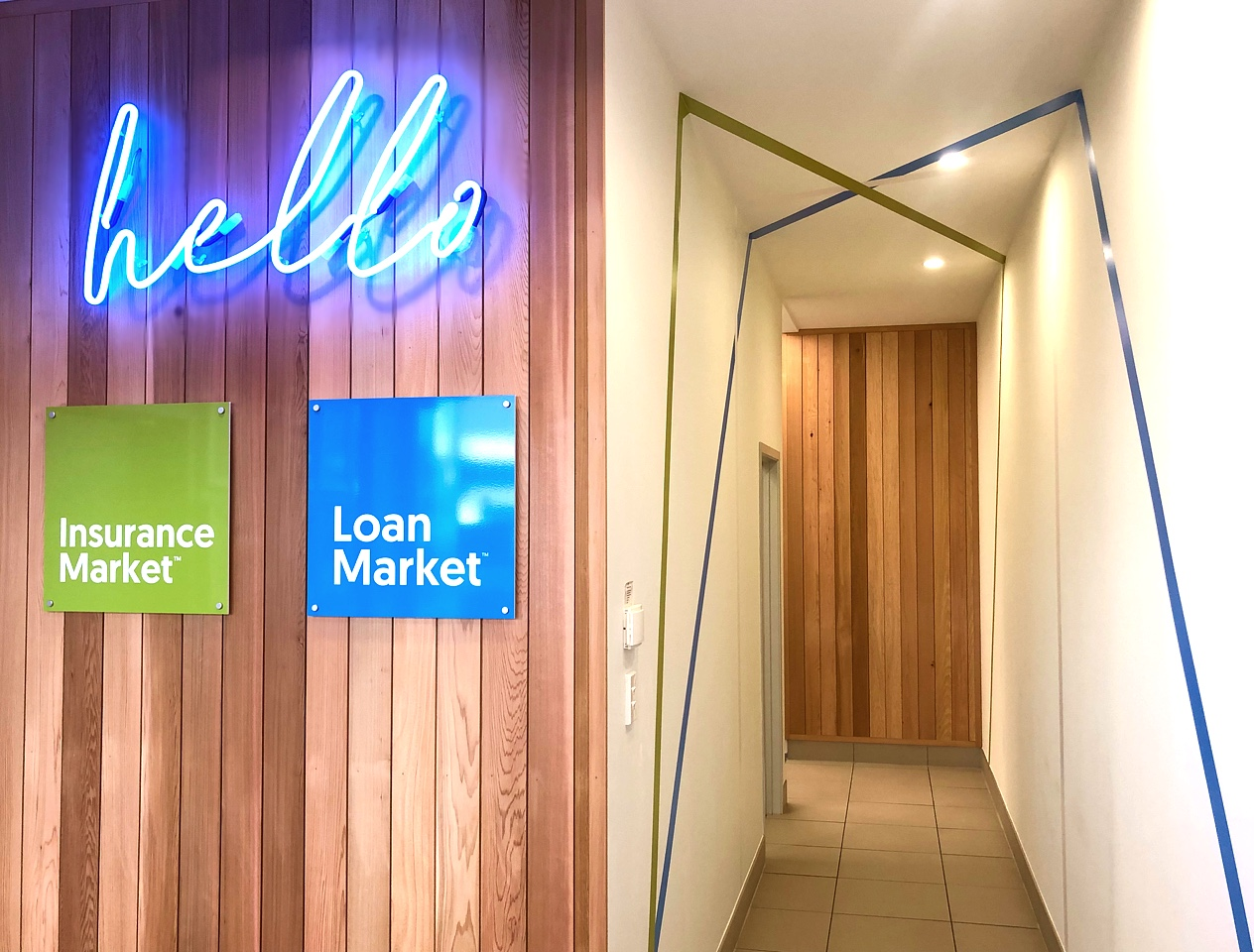 modern office hallway with blue neon hello sign on cedar wood panelling and blue and green stripe wall decals