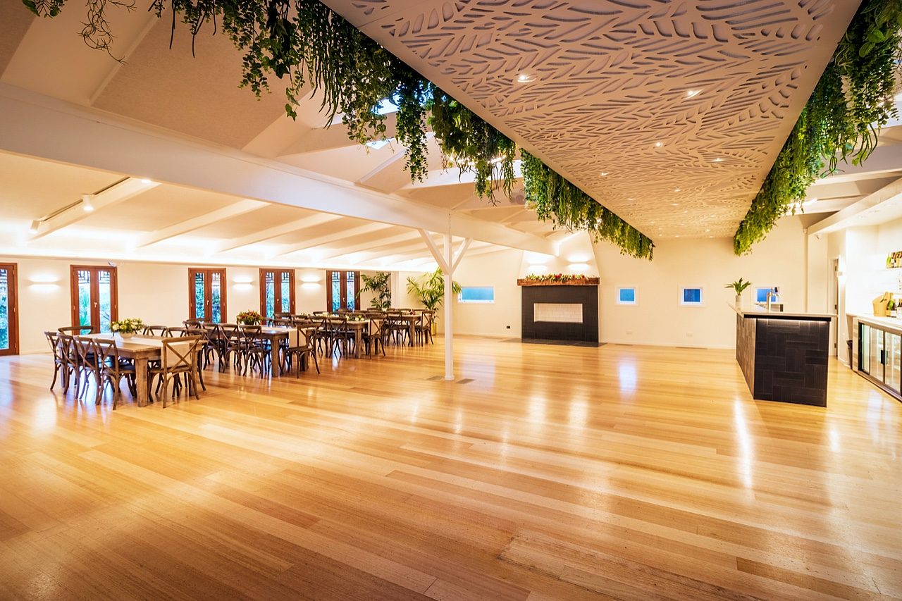 wedding venue main hall with polished wood floors, open fireplace, laser cut ceiling and hanging plants