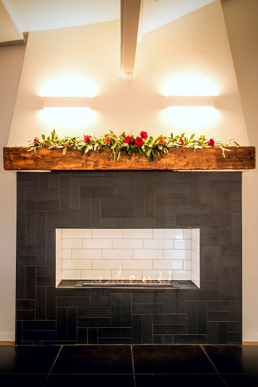 open fire with wooden heart and black patterned tiles