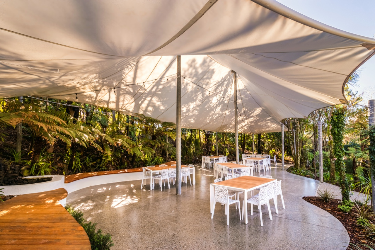 wedding venue outdoor space with concrete floor, wood bench seating, white tent and modern dining table settings