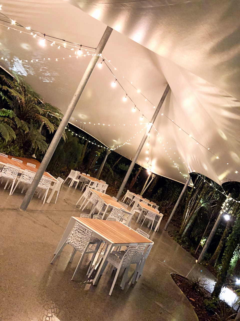 wedding venue at night with lights under white tent and modern dining table settings