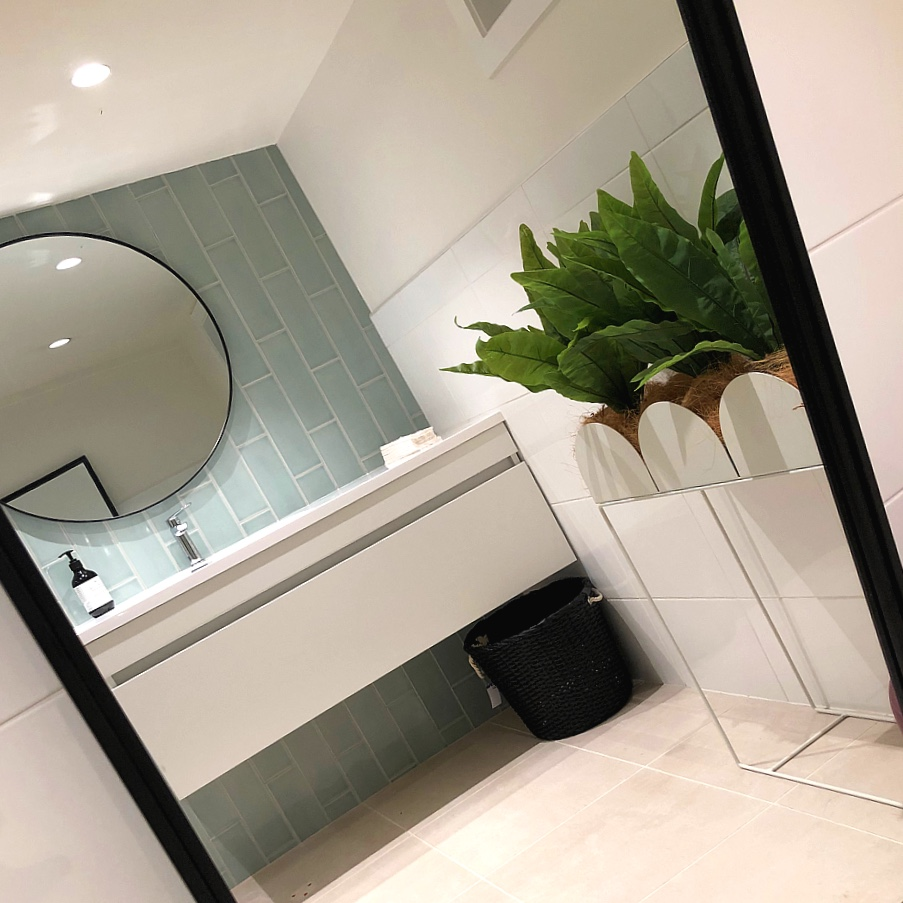 clean modern bathroom with blue glass tiles, metal planter box and round mirror