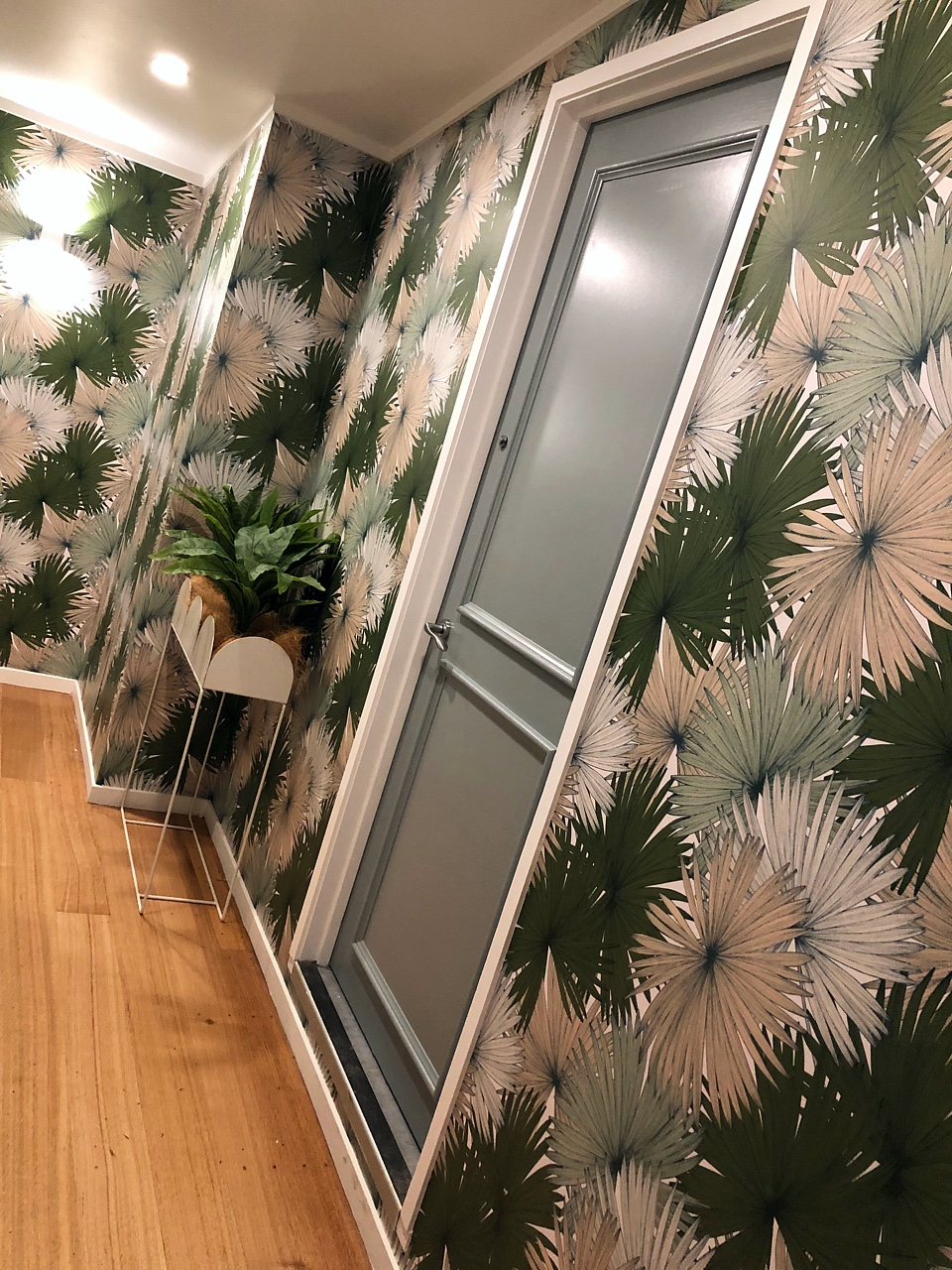 hallway design with palm leaves wallpaper and planter box