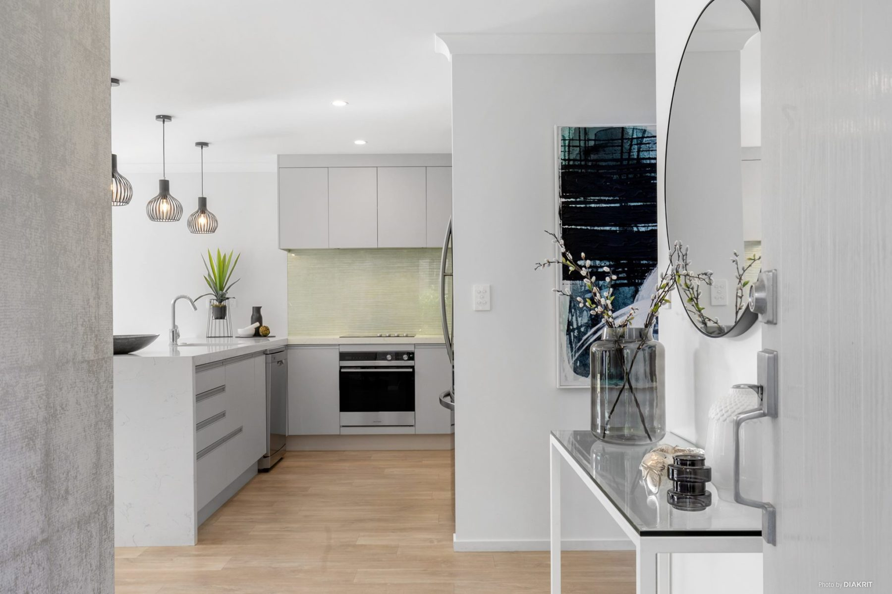 new build entrance hall and modern kitchen with modern art, glass console table and round mirror