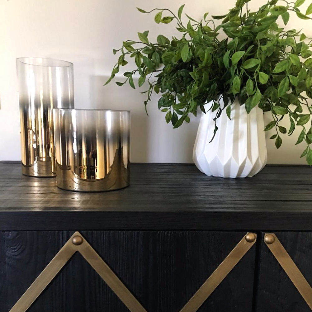interior styling of a black buffet unit with plant and gold accessories