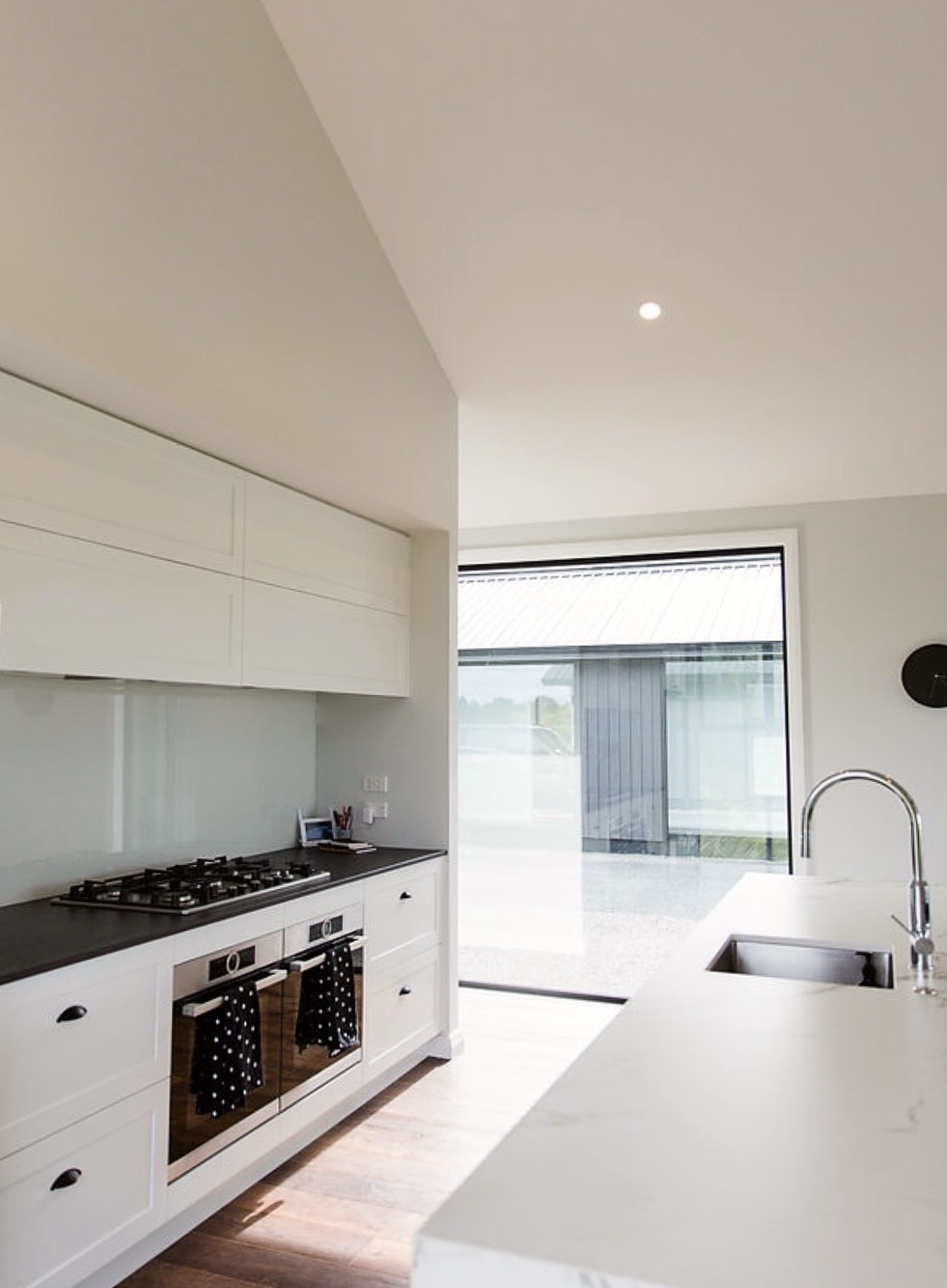 new build modern take on traditional white kitchen with corian benchtop
