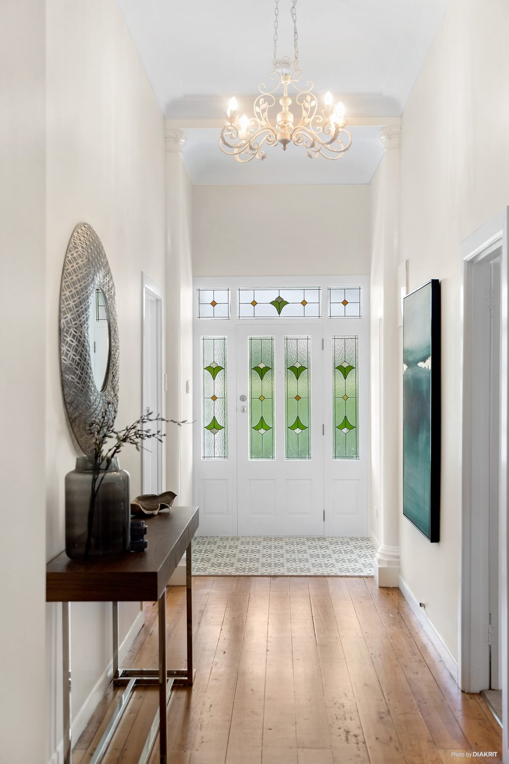 entrance hallway in traditional villa with stained glass door and original wood floors