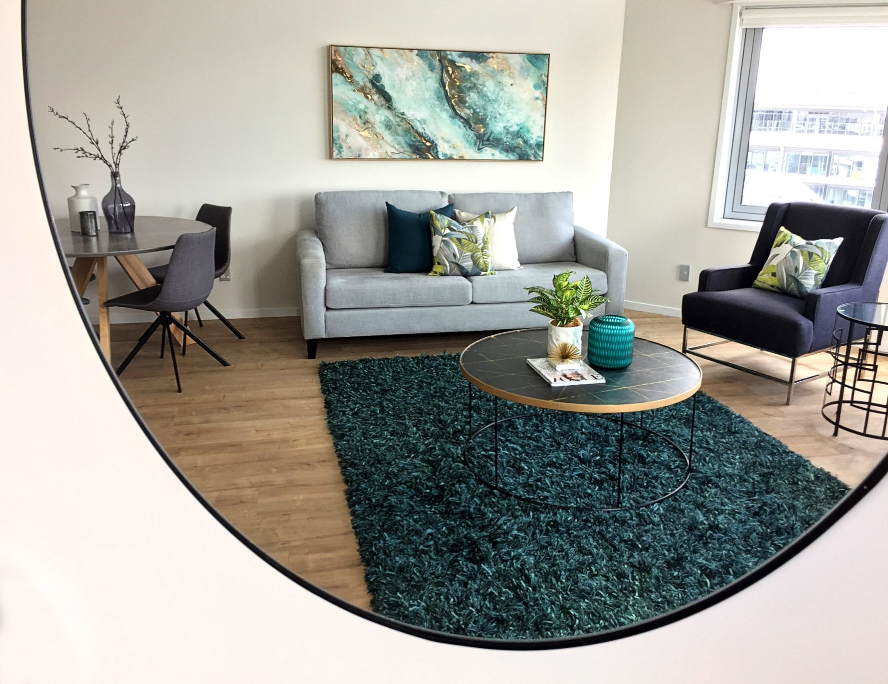 mirror reflection of living room with teal rug and wood floors