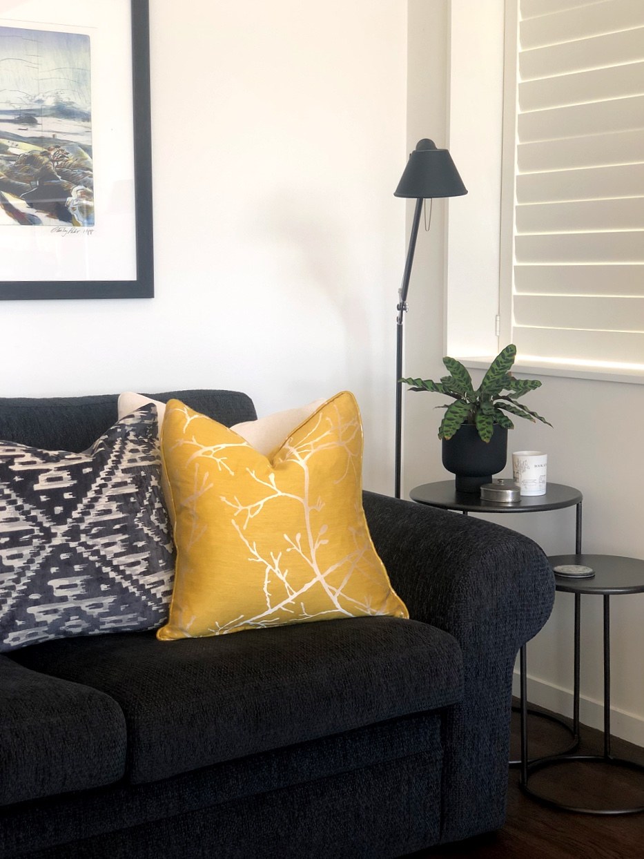 patterned cushions on black living room couch