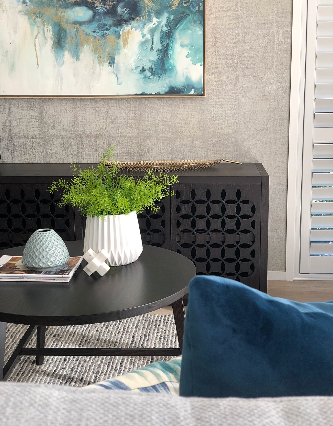 living room with black coffee table and carved sideboard