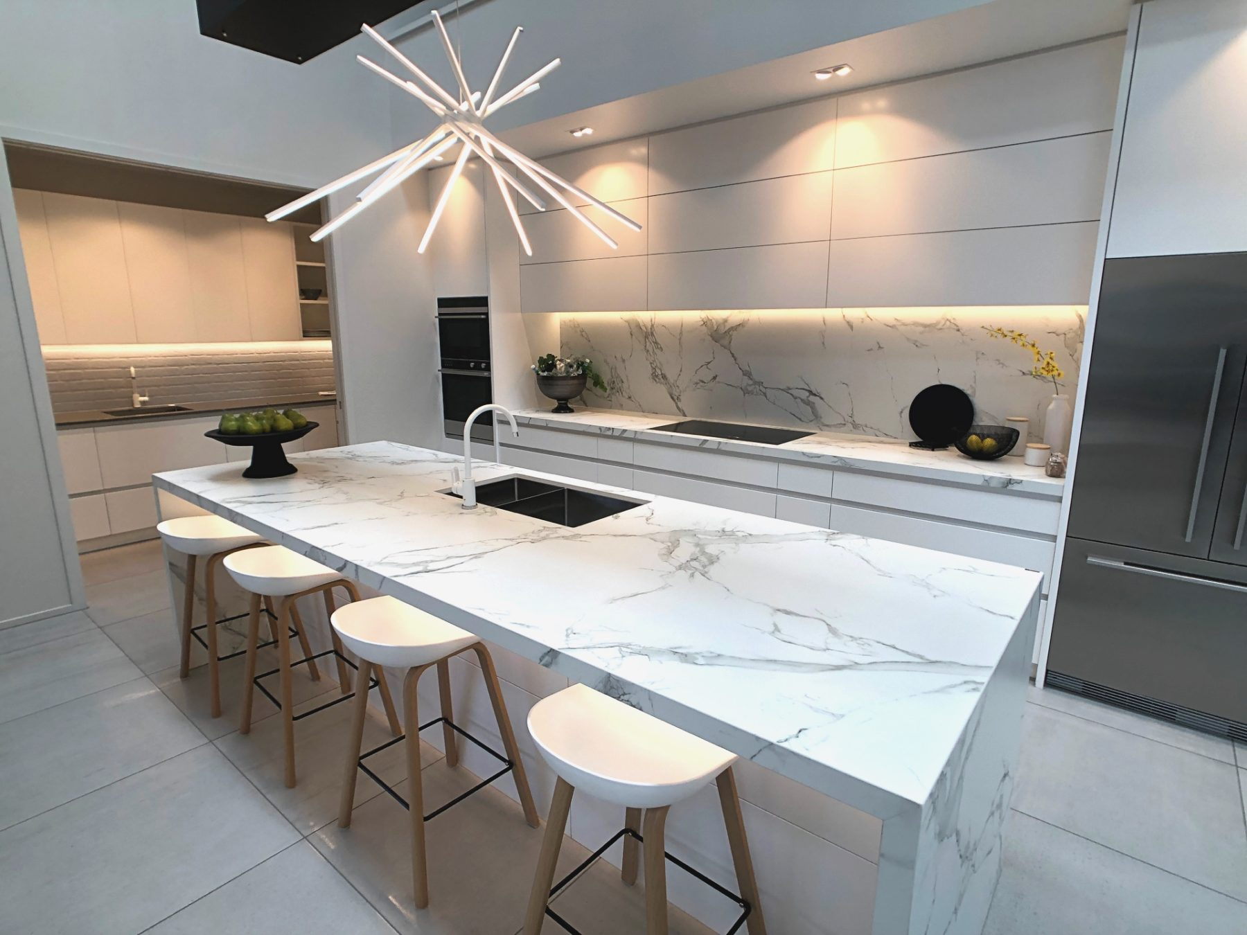 modern white marble kitchen with island and barstools