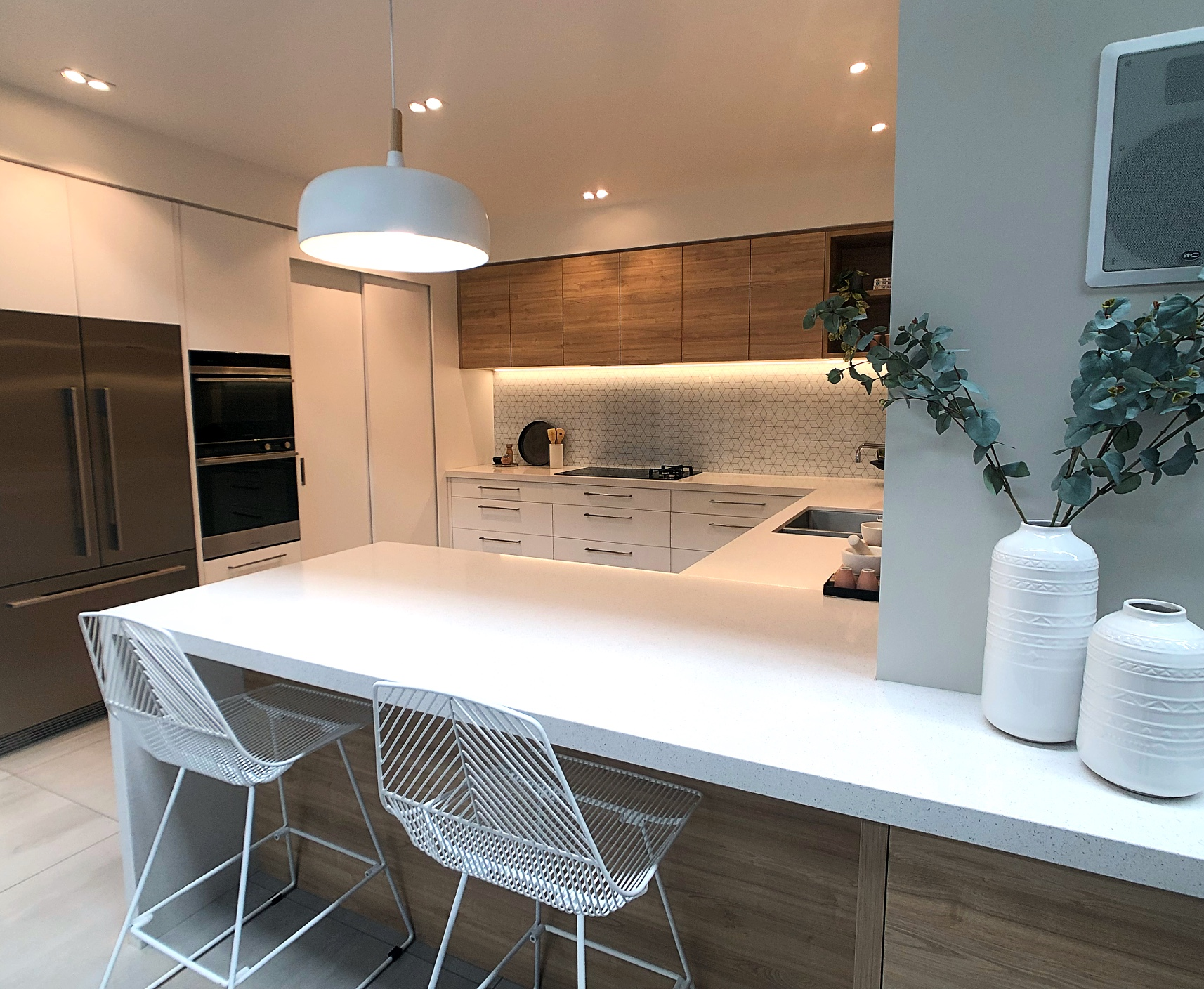 modern kitchen with wood doors and white stone tops