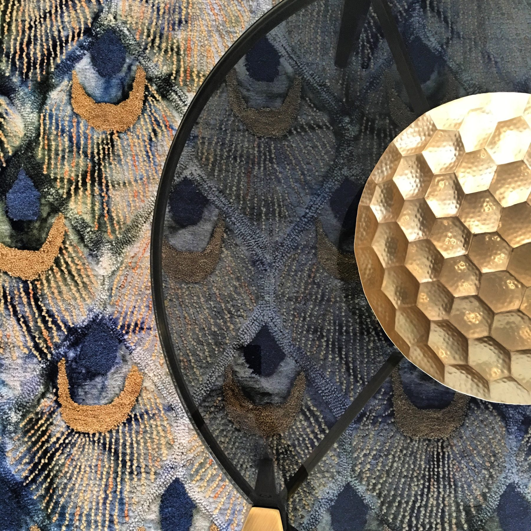 birds eye view of peacock rug with glass coffee table and gold bowl