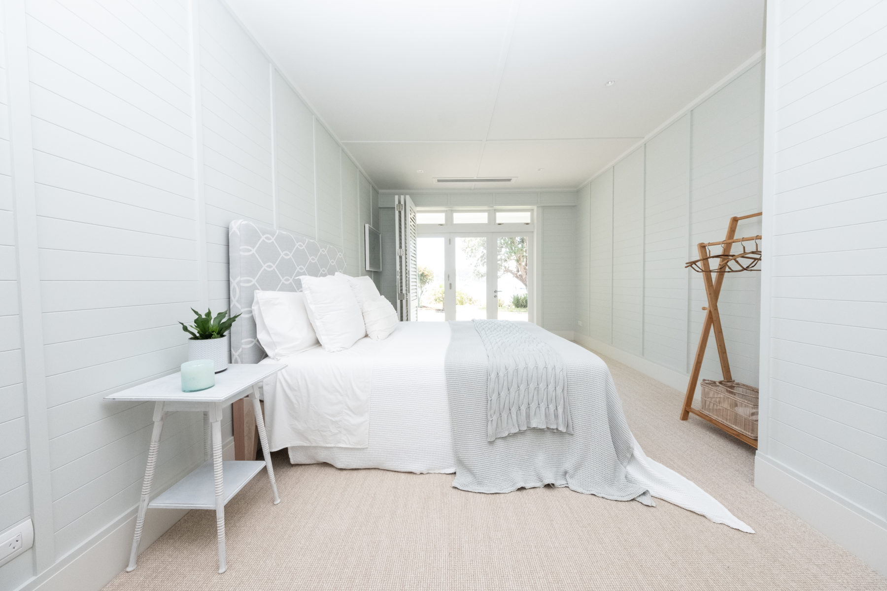 modern beach house bedroom with panelled walls and coir carpet