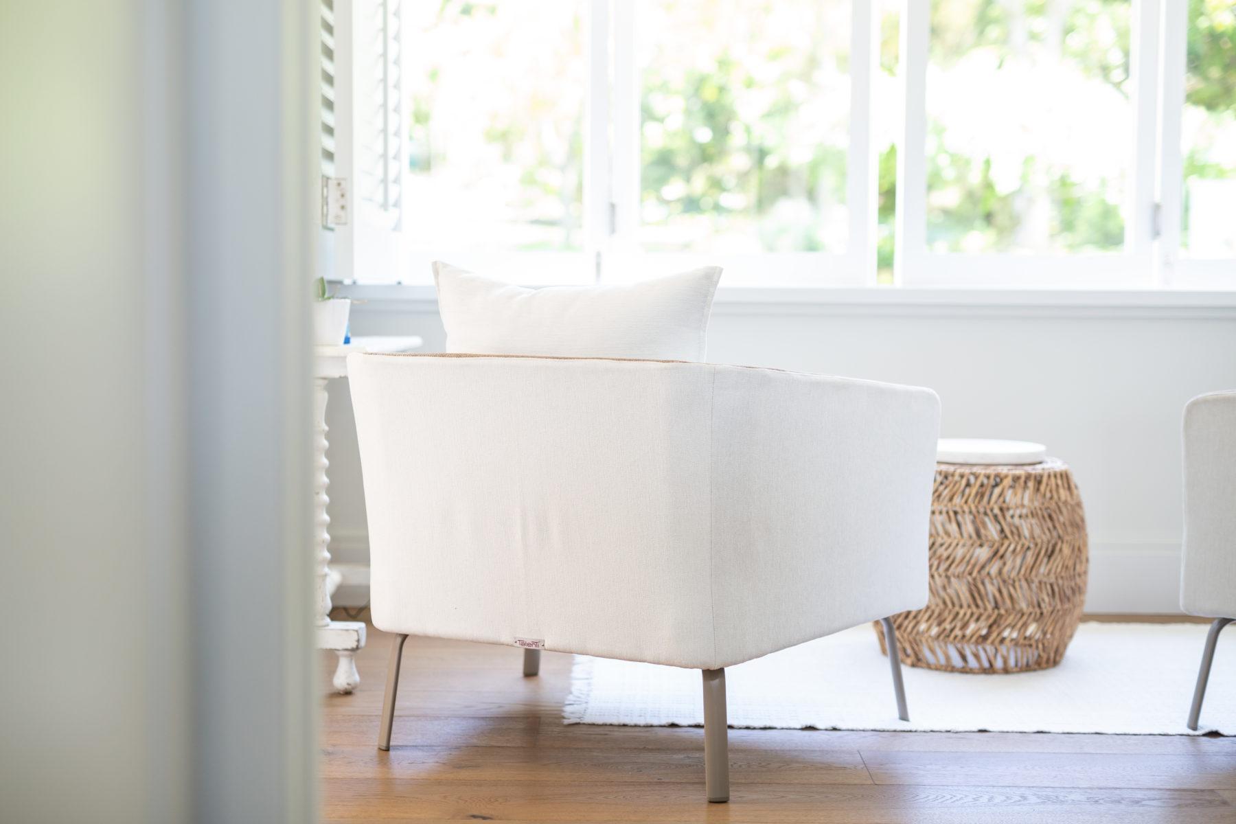 custom white chair with rattan side table and wood flooring modern beach feel