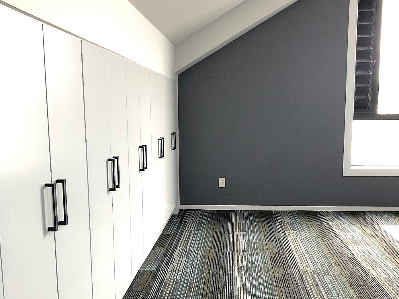commercial office space with built in storage and stripe carpet