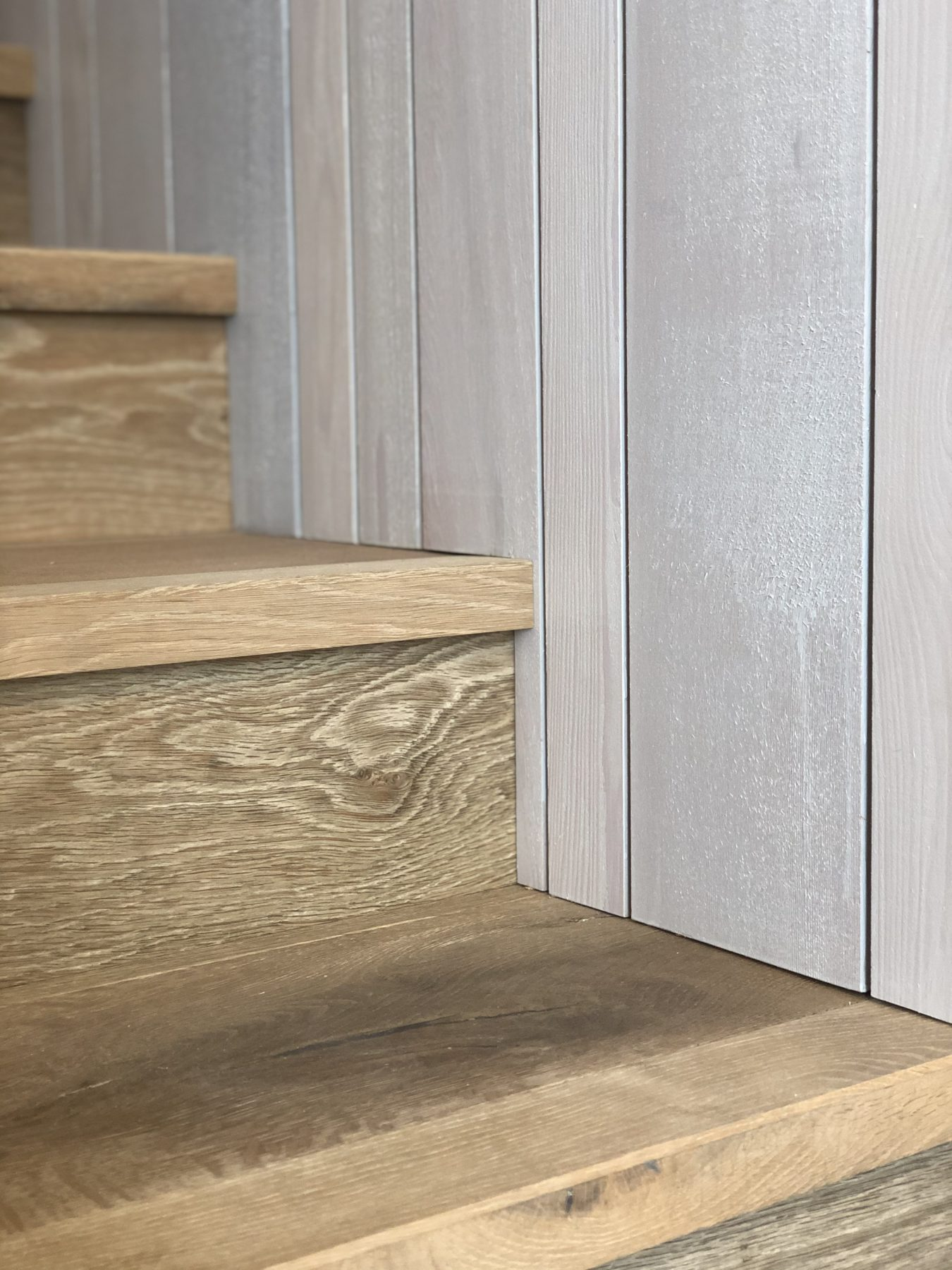 closeup of wood stair tread and wood wall panels