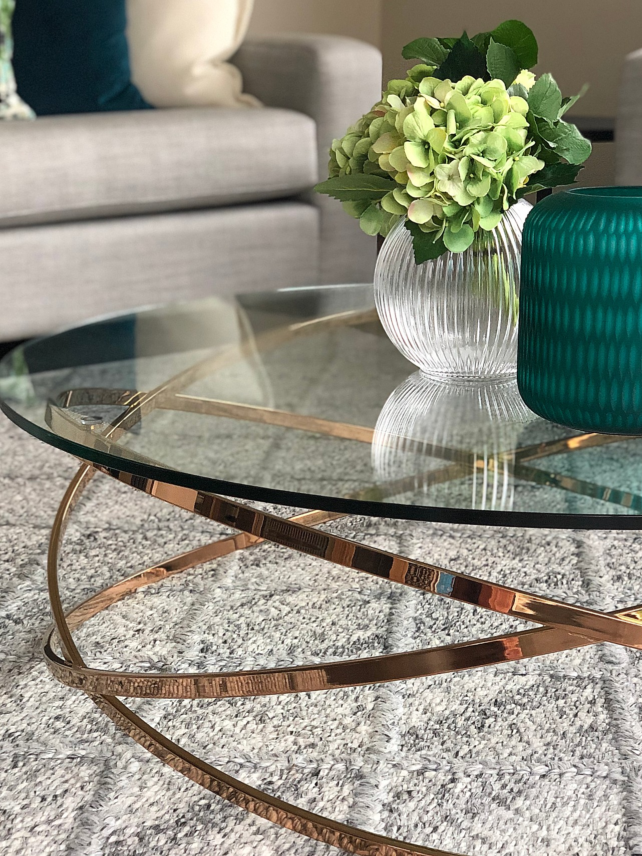 elegant modern living room with rose gold glass coffee table and teal accessories