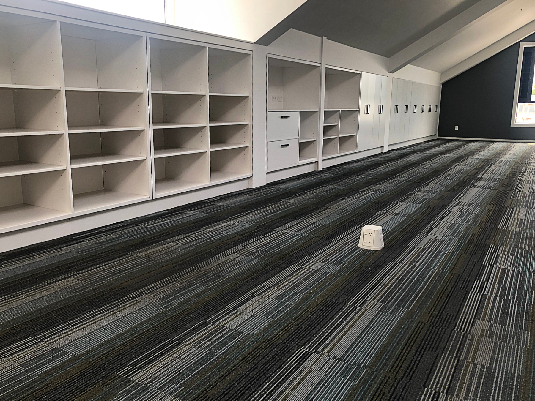 modern office space with stripe carpet and white built in cabinetry