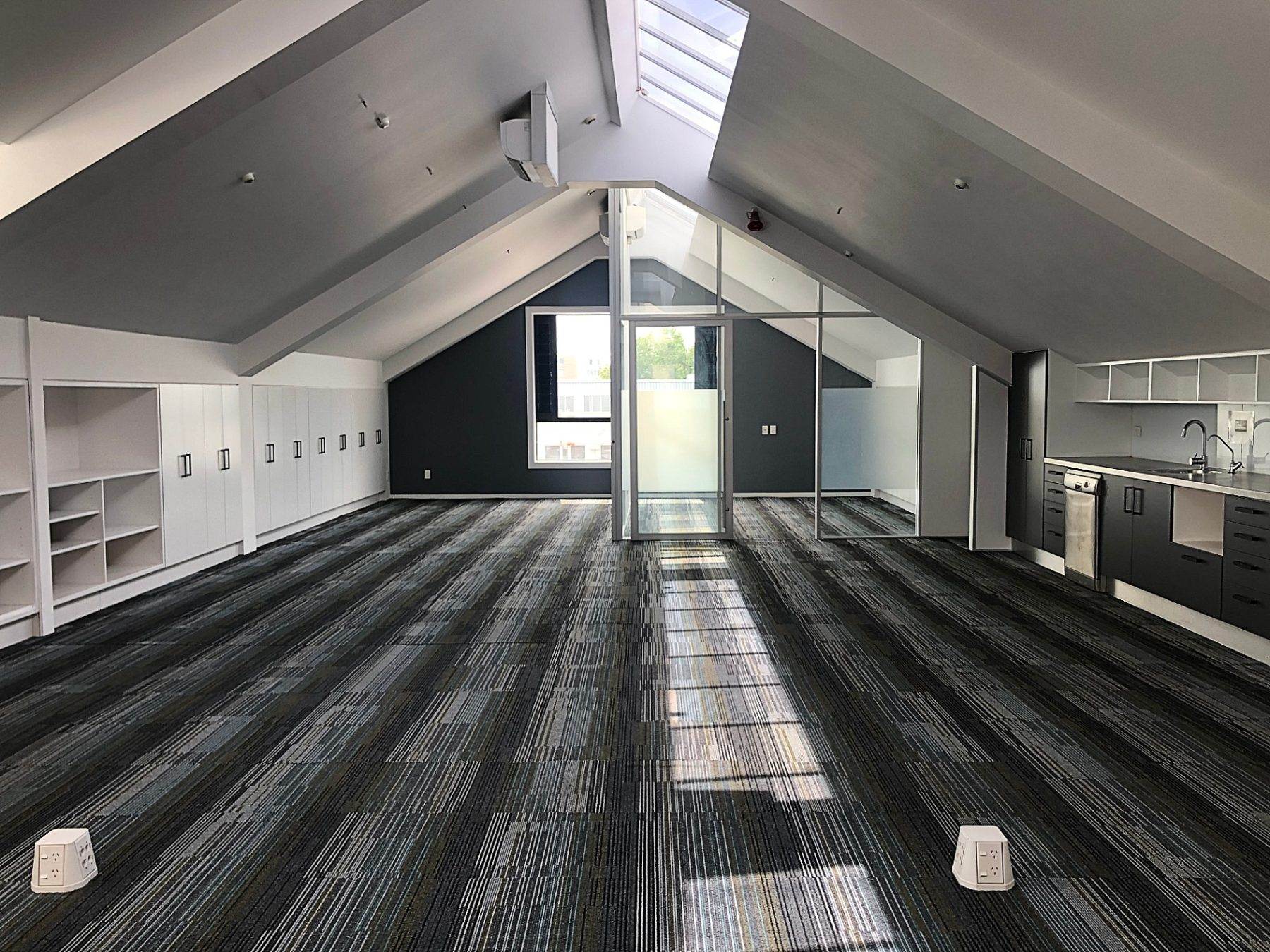 modern office space with built in storage, stripe carpet and glass doors