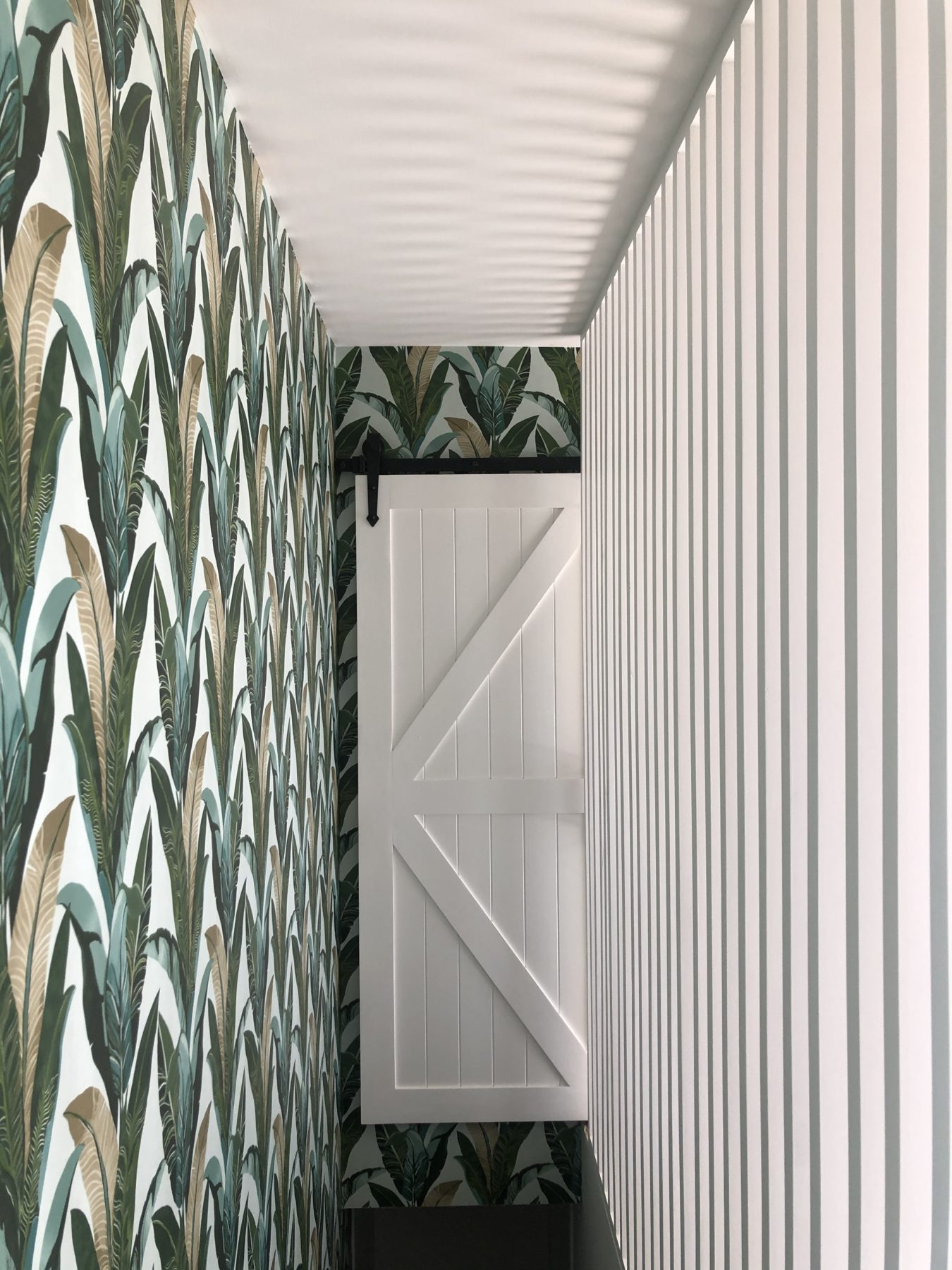 modern hallways and stairwell with wood slat detailing and banana leaf wallpaper