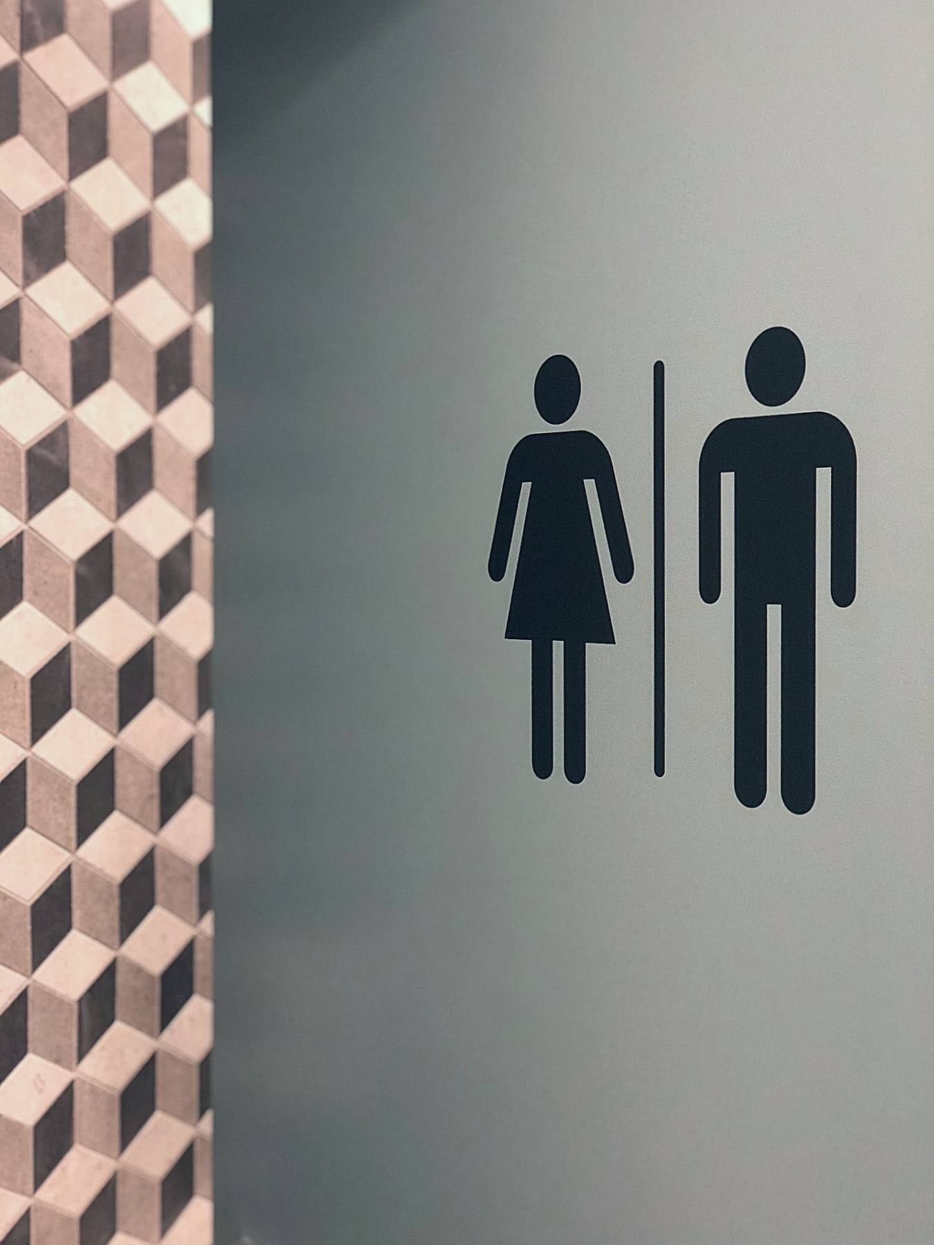 male and female toilet door sign with geometric tiles