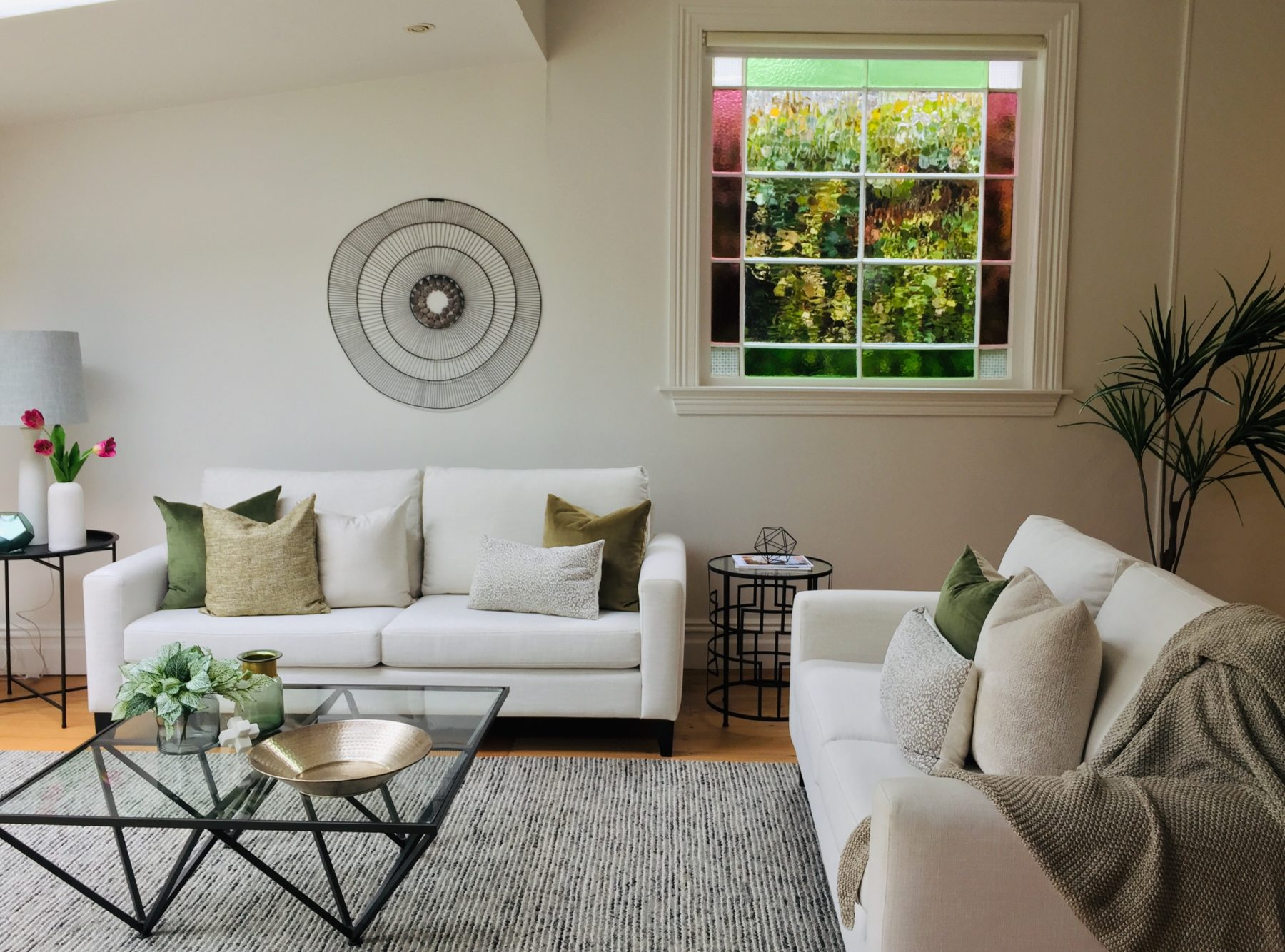 traditional villa living room with stained glass window and modern white couches