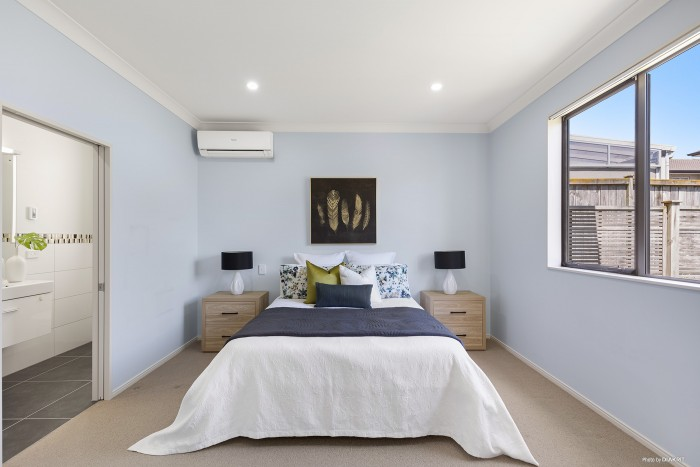 modern bedroom with grey blue and green bedding and light blue walls